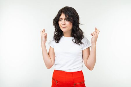 brunette girl in a white t-shirt worries on a white background.