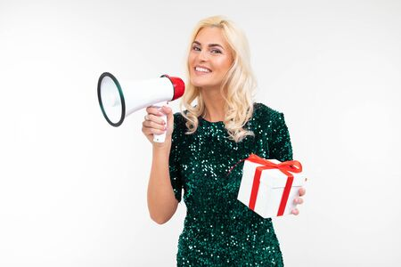 joyful girl in a dress announces gifts in a megaphone holding a gift box on a white studio background. Zdjęcie Seryjne