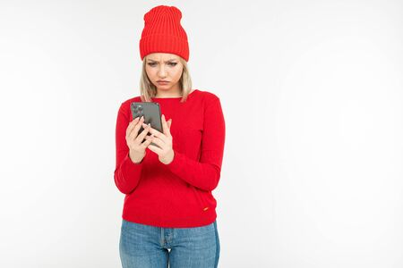 surprised girl in red clothes surfing the internet on a white background with copy space. Zdjęcie Seryjne