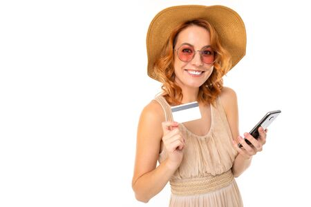 Portrait of caucasian female with fair red hair, pretty face in beautiful light dress and big hat smiles and shows her phone with credit card Zdjęcie Seryjne