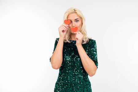 blonde playing sexy girl in a green dress holding a paper red heart on a white background with copy space.