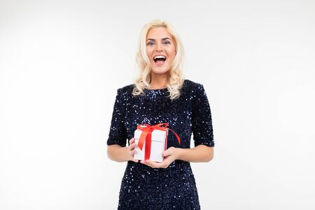 blond Caucasian woman in a blue shiny dress joyfully holds a received gift box on a white background with copy space.