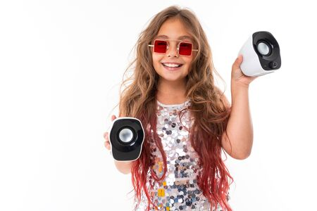Little beautiful caucasian girl with long wavy chestnut hair and nice smile listens to music Zdjęcie Seryjne