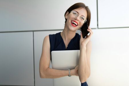 Picture of beautiful woman with short dark hair in office suit made an appointment and is waiting for colleague near their office