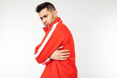 man in a sports red suit hugs himself to keep warm on a white background with copy space.