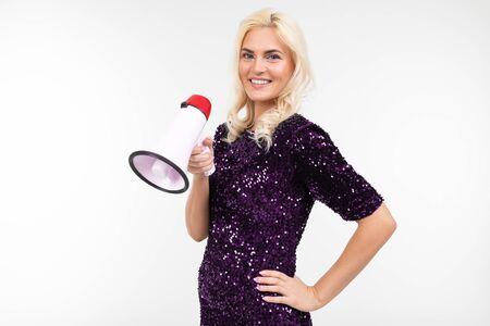 blond girl with a megaphone presents news on a white background with copy space. Zdjęcie Seryjne