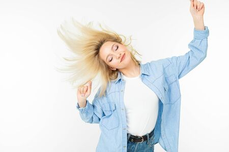 girl in a stylish image waving her hair and dancing on a white studio background.