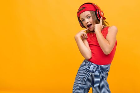 teen girl enjoys music on headphones and dances on a yellow background with copy space. Zdjęcie Seryjne