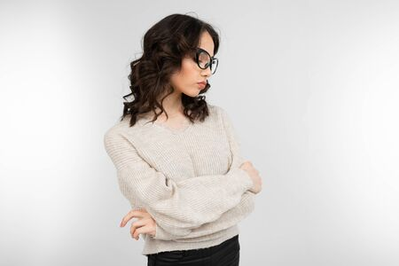 attractive brunette girl in stylish glasses for vision poses on a gray background with copy space.