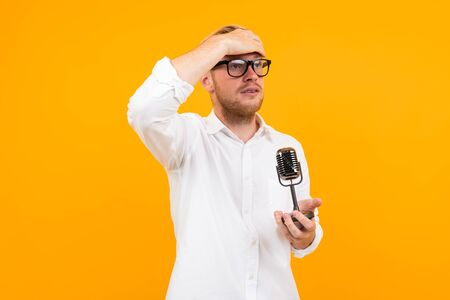 blond guy in a white shirt thoughtfully holds a retro microphone on a yellow background with copy space. Zdjęcie Seryjne