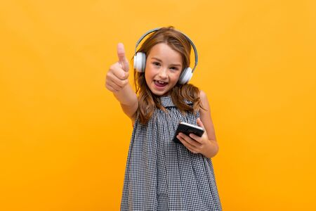 blond teen girl listens to music in large headphones on a subscription in a playlist phone on a yellow background. Zdjęcie Seryjne