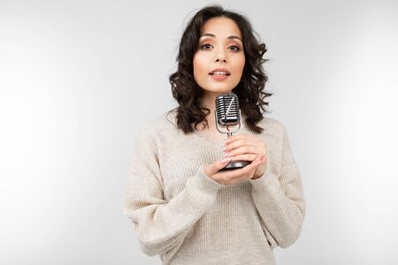 brunette girl in a white sweater holds a retro microphone in her hand and sings a song on a white background. Zdjęcie Seryjne
