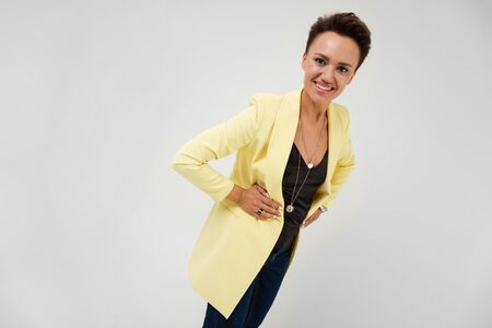 Handsome woman in yellow blazer and black dress smiles, isolated on white background.