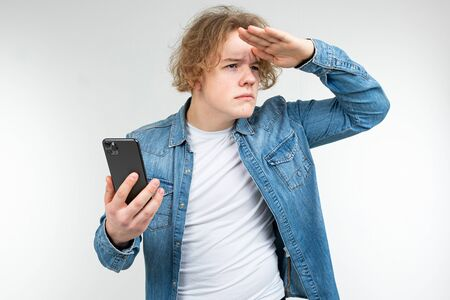 guy with a phone in his hands looks around on a white studio background. Zdjęcie Seryjne