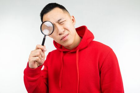 brunette man in a red sweater looking at the camera through a magnifying glass on a white isolated background.