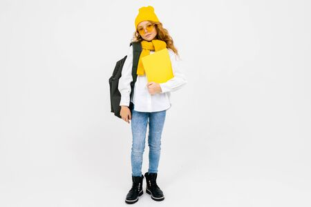 teenager girl with books in hand and a backpack on his shoulders on a white isolated background.