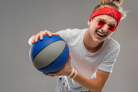 cool blond guy in a white t-shirt with a basketball on a gray background.
