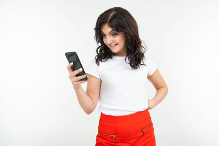 young brunette woman in a white t-shirt looks doubtfully attentively at a smartphone holding it in her hand on a white isolated background with copy space. Banque d'images