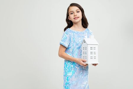 teenager girl with a figure at home on a white background with copy space. immovable property.