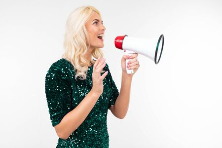 stylish girl in a green dress speaks in a megaphone attracting attention on an isolated white background.