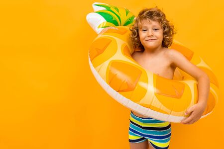 Little boy with curly hair in swimsuit with big rubber circle isolated on yellow background.