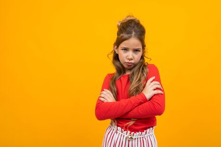 offended teenager girl crossed her arms on a yellow background with copy space.
