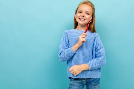 smiling european girl holding a toothbrush in her hands on a light blue background with copyspace. Stockfoto