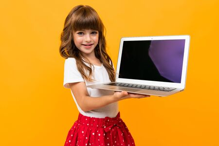 Portrait of charming caucasian girl with long chestnut hair and pretty face in white and red dress holds a laptop and smiles