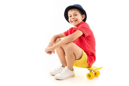 attractive young boy sitting on a yellow skateboard on a white background. Banco de Imagens