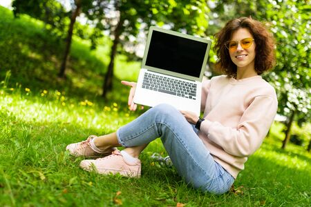freelancer is sitting on the grass in a summer park holding a laptop screen forward with a mock up.