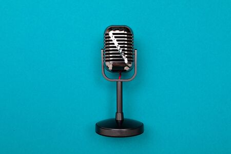 Black microphone isolated on blue background. Imagens