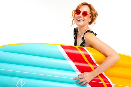 lovely girl in retro glasses holds a surfboard on a white studio background. 免版税图像