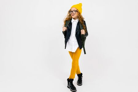European attractive girl dressed in a yellow hat, glasses and a leather jacket with a backpack on his back in full growth on a white background with copyspace. Imagens