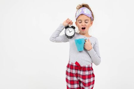 sleepy girl in pajamas just woke up and yawns on a white background with copy space.