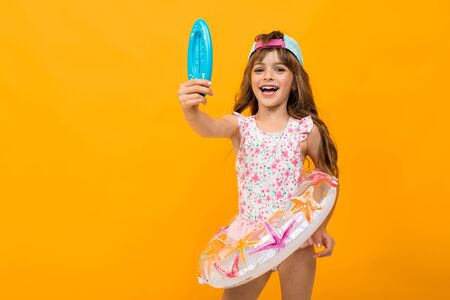child with a baseball cap in a swimsuit with a swimming circle holds a thermometer for water on a yellow clean background.