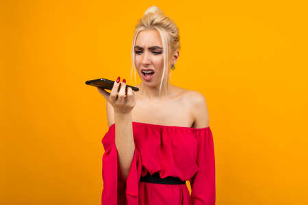 girl in a red dress indignantly speaks on the phone on a yellow studio background Фото со стока