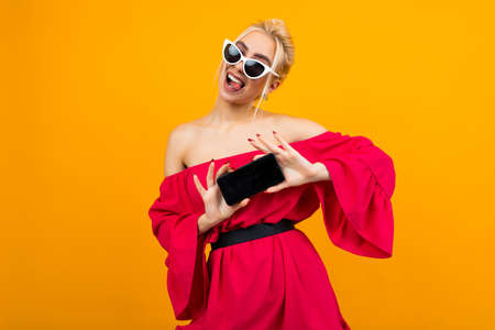 attractive girl in a red dress shows a blank screen phone template on a yellow background with copy space 免版税图像