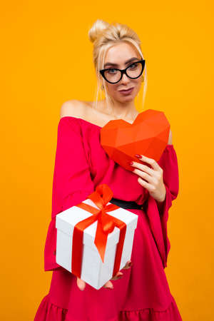attractive european girl in red dress holds gift box and red paper heart on orange studio background