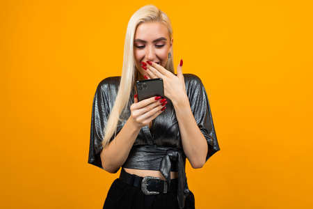 European stylish charming girl in surprise reads messages on her smartphone on a yellow studio background Фото со стока