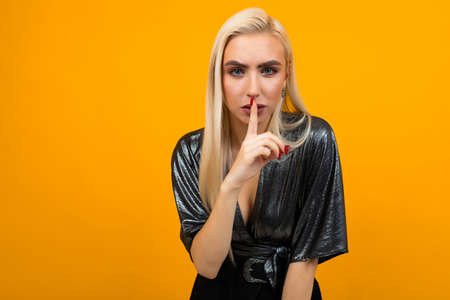 portrait of a blond young woman asking for silence on a yellow studio background