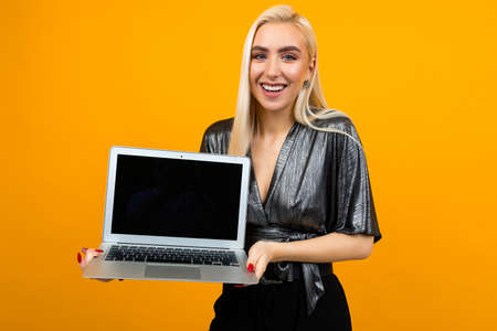 smiling charming blond girl holding a laptop screen blank on a yellow wall background