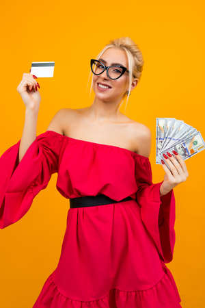 blond sexy girl in a red dress with bare shoulders holds a bunch of loan money and a credit card credit mockup on an isolated studio background 免版税图像