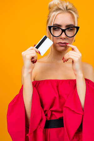 attractive girl in a red dress holds a credit card with a layout for the bank on a yellow background 免版税图像