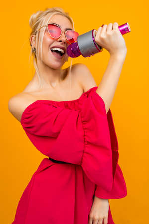 European blond girl singer in a bright red dress with manicure with a microphone in her hands on a yellow studio background