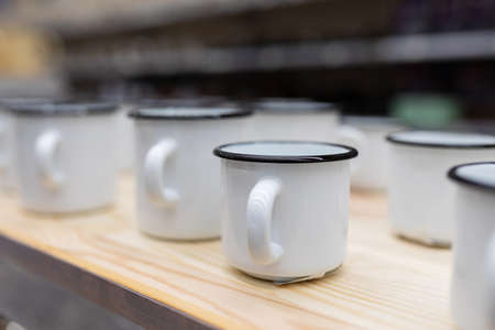 white metal enameled mugs standing on a store counter.