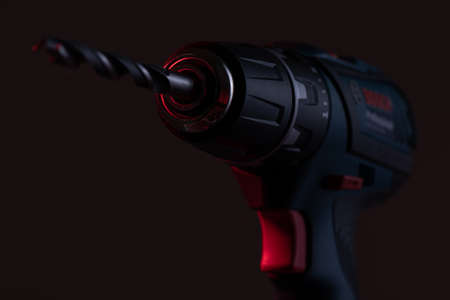 powerful drill with a drill inserted close up on a dark background. Stok Fotoğraf