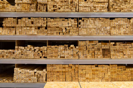 shelves of a hardware store lined with stacks of wooden boards.