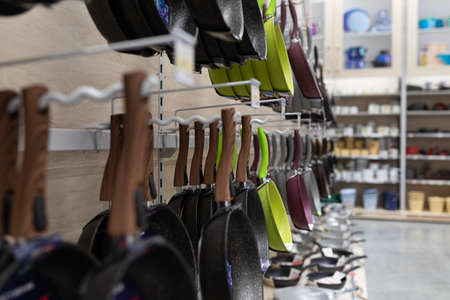 a large selection of kitchen utensils on store shelves. Фото со стока