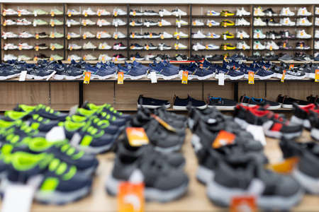 large shoe store with long shelves filled with shoes. Foto de archivo