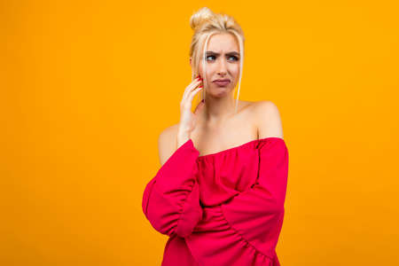sexy excited blonde girl in a red dress on a yellow studio background 免版税图像